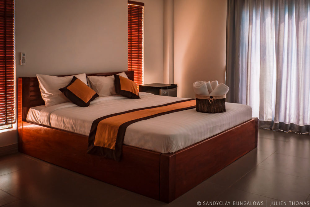 Single bedroom with air conditioner, small fridge, large curtains for a totally privacy and many others commodity for the guests in Sandyclay Bungalows.