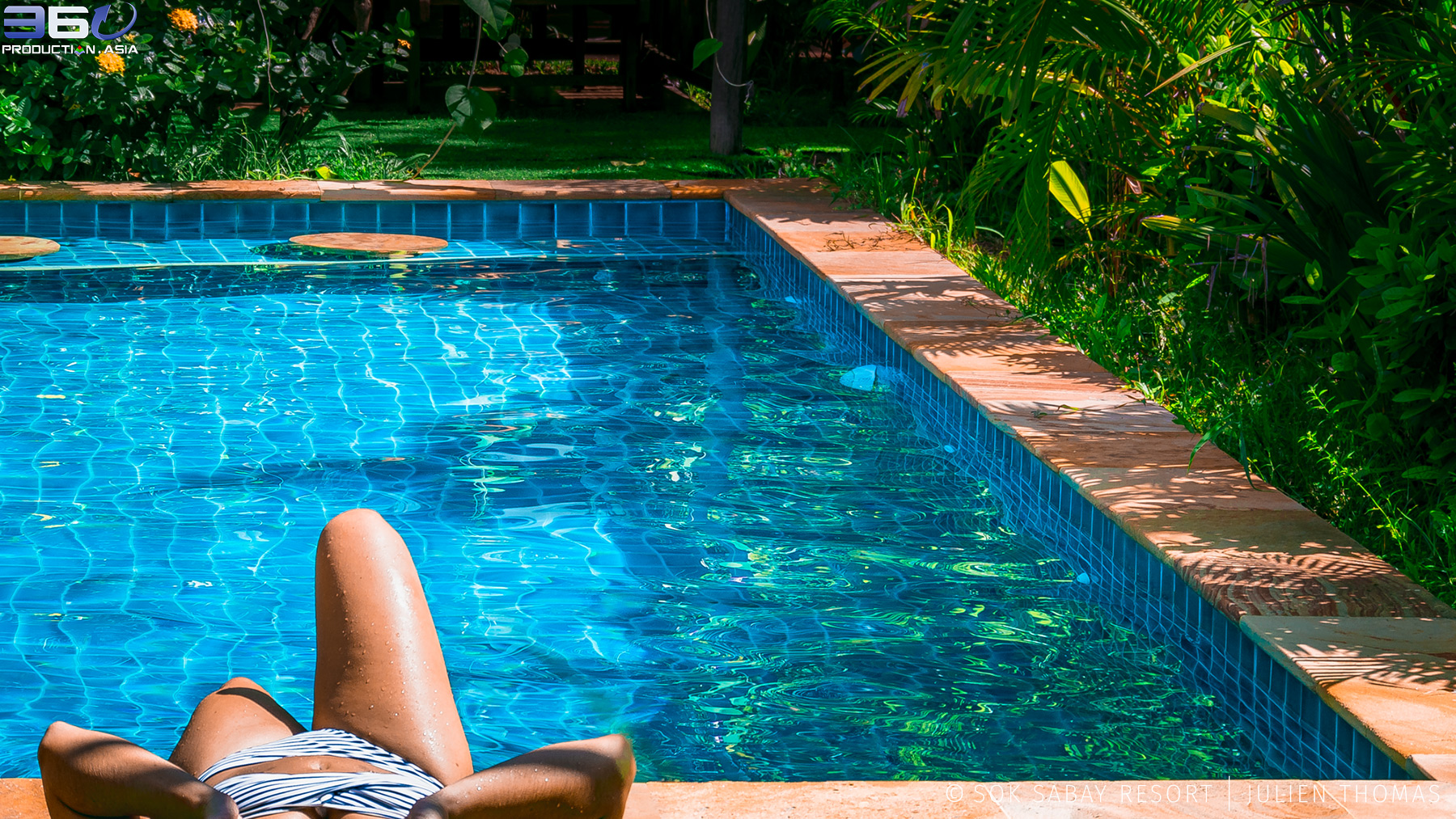 Guest who is relaxing in the hotel swimming pool surrounded by tropical vegetation in Sok Sabay Resort, Otres Village - Sihanoukville Province.