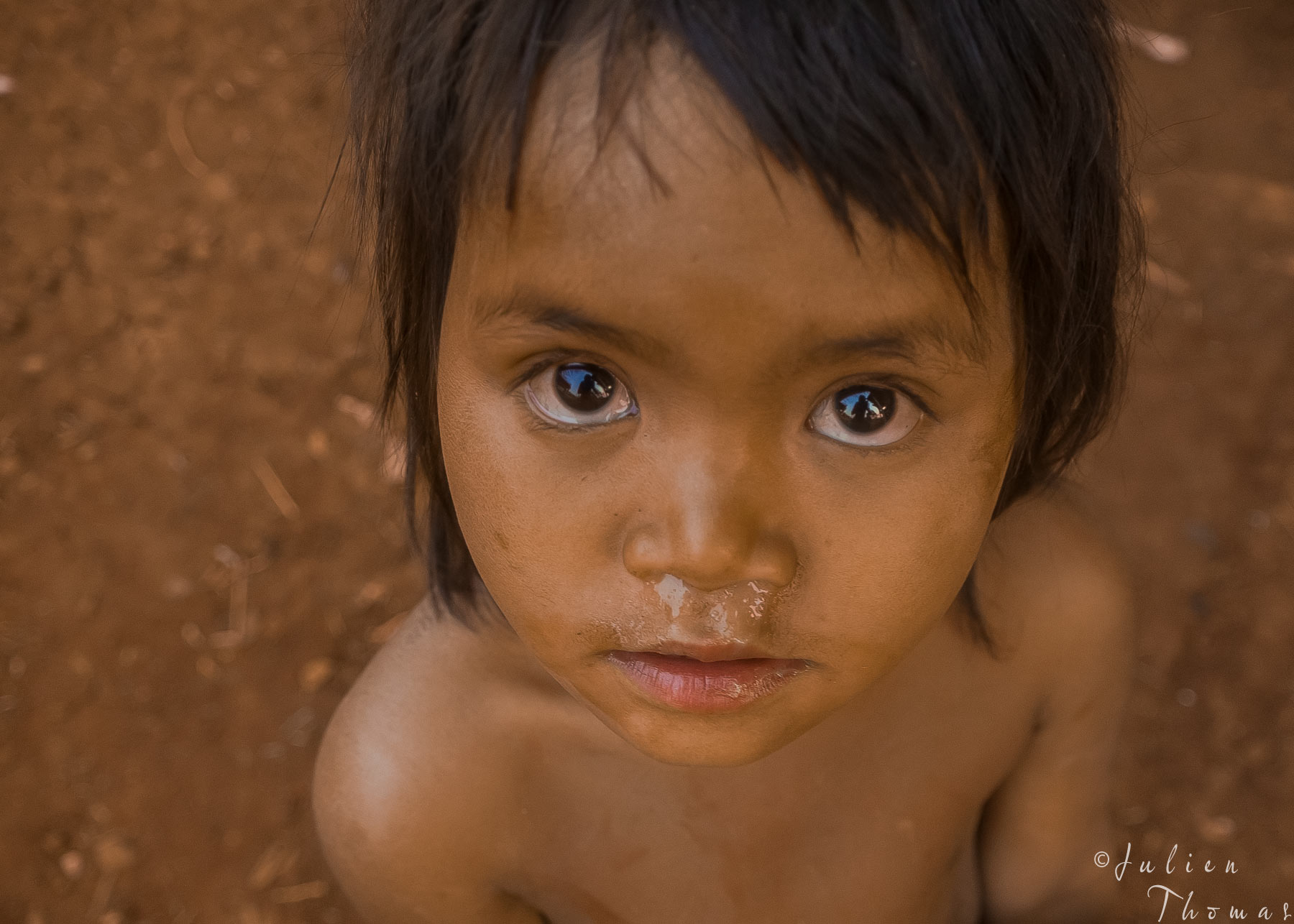 Underprivileged child from an animist Katou minority in Laos, staring at the photographer and its camera. Its possible to shape Julien Thomas in her eyes.