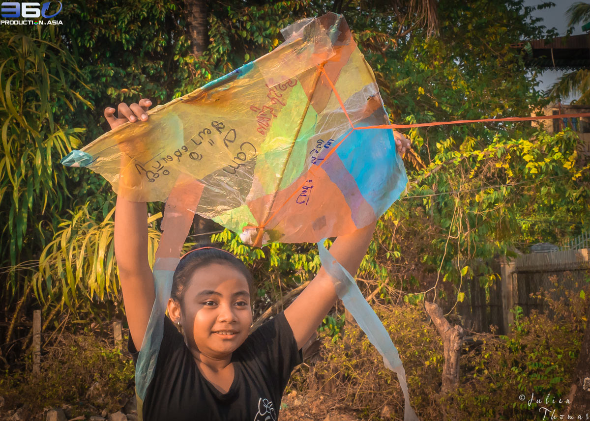 Young Cambodian girl is holding a homemade kite made with recycle multicolor plastic waste, ready to take off and to fly.