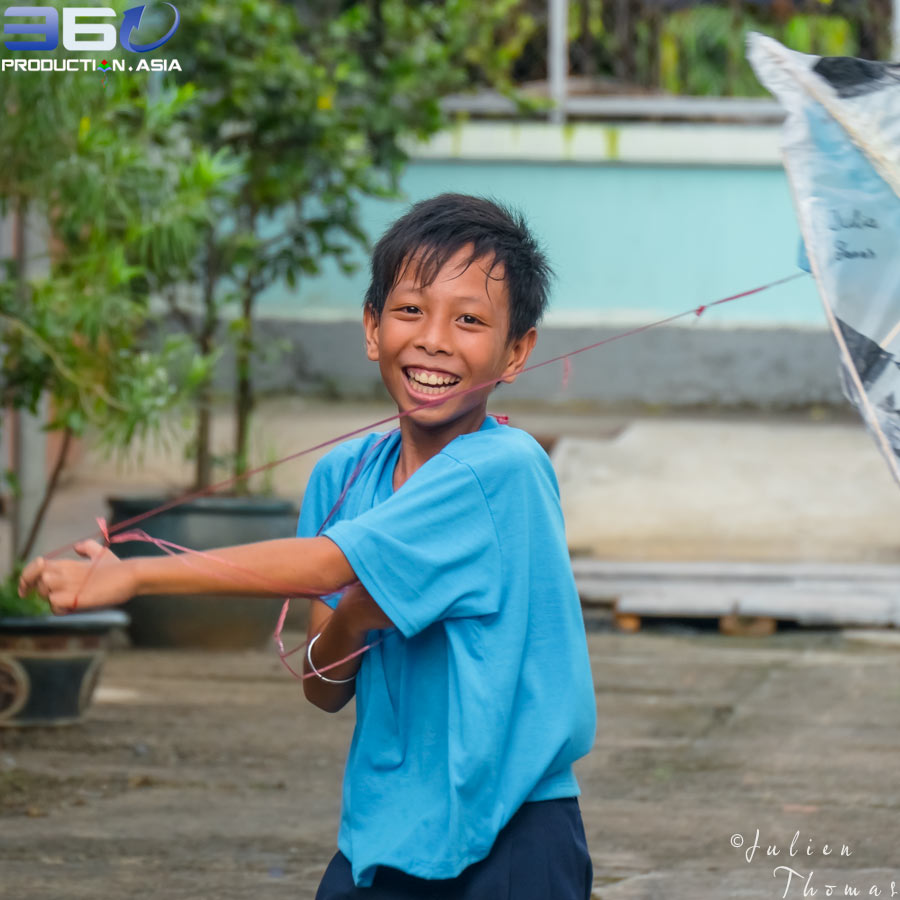Smiley Vietnamese child enjoying to play with his homemade kite he have created with recycled plastic waste during a fun filled ecological project for children.
