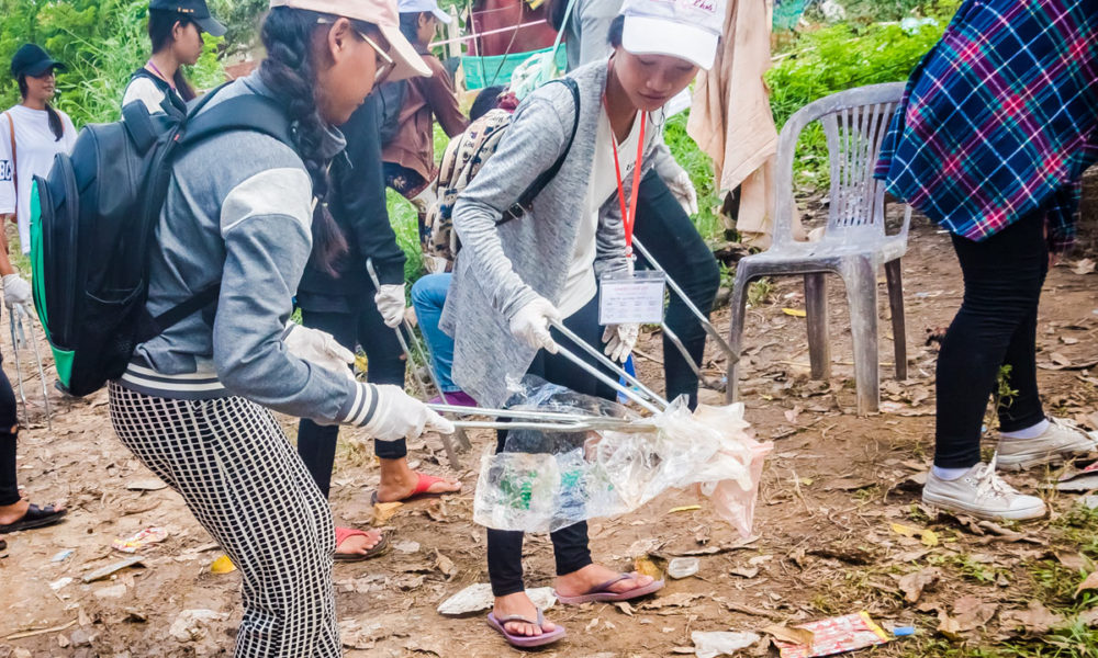 """Underprivileged schoolgirls from NGO """"Toutes à L'école"""" are collecting discarded waste in their neighborhood community during an ecological course in Cambodia."""