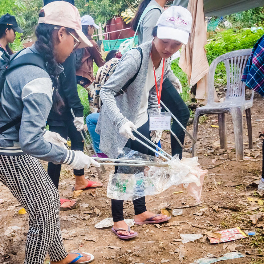 "Underprivileged schoolgirls from NGO ""Toutes à L'école"" are collecting discarded waste in their neighborhood community during an ecological course in Cambodia."