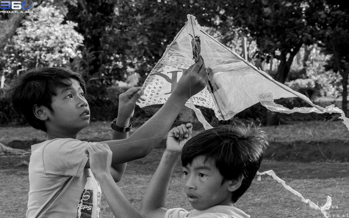 Underprivileged schoolchildren in Cambodia are playing with a kite made from plastic waste - Louis Vuitton bag upcycled into a children's craft for goods.