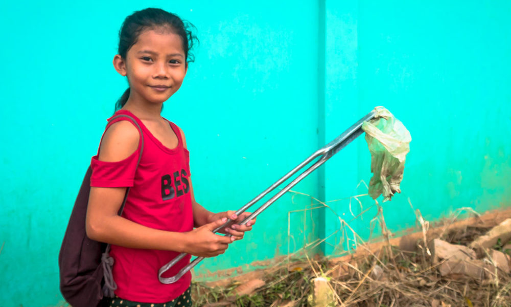 Young girl in Cambodia is picking up discarded plastic waste near her school for a creative and ecological course - children's craft project in Phnom Penh.