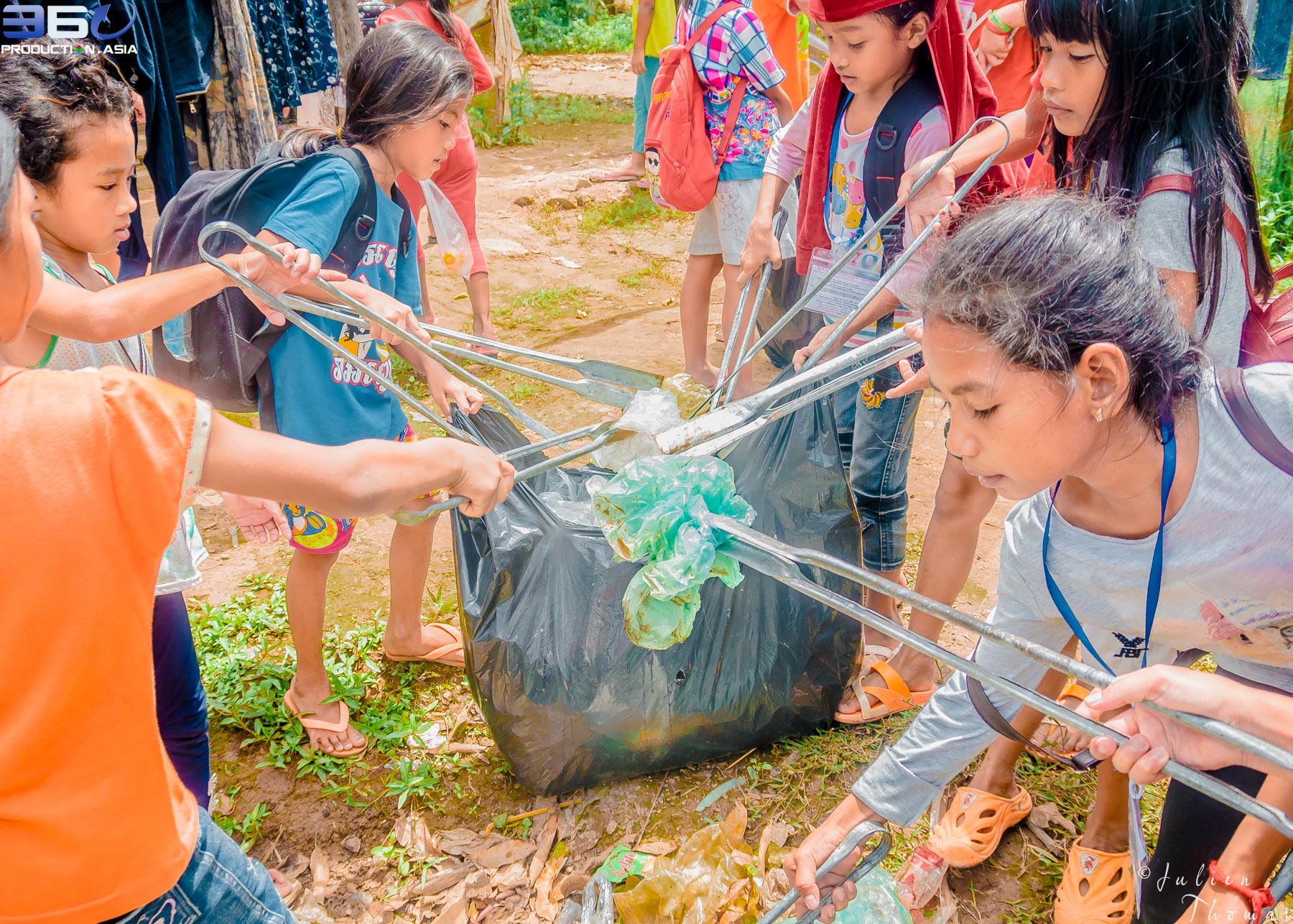 Group of young Cambodian schoolchildren are picking up discarded plastic waste - plastic bags in their community for a recycle and ecological course at school.