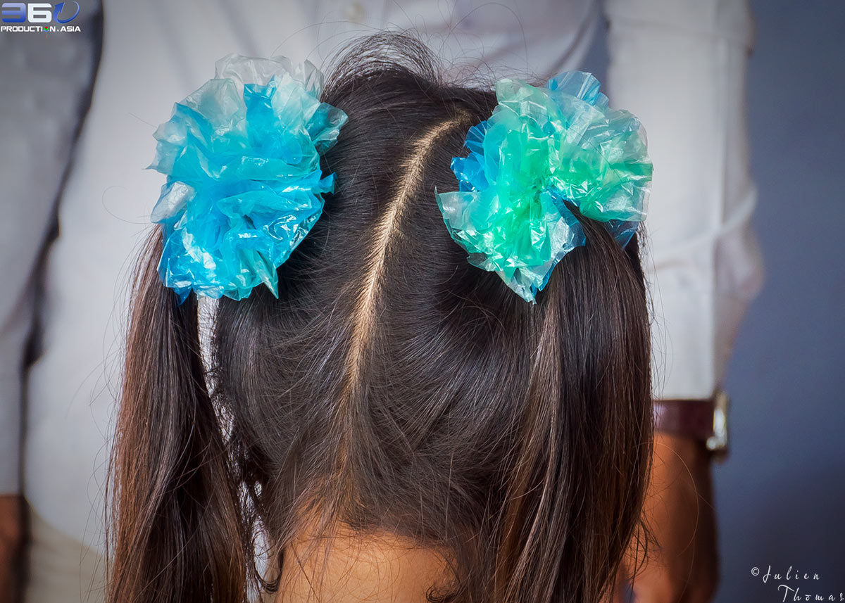 Cambodian child is wearing two hair bunches crafted with plastic waste - plastic bags during a creative and ecological children's course in Sihanoukville