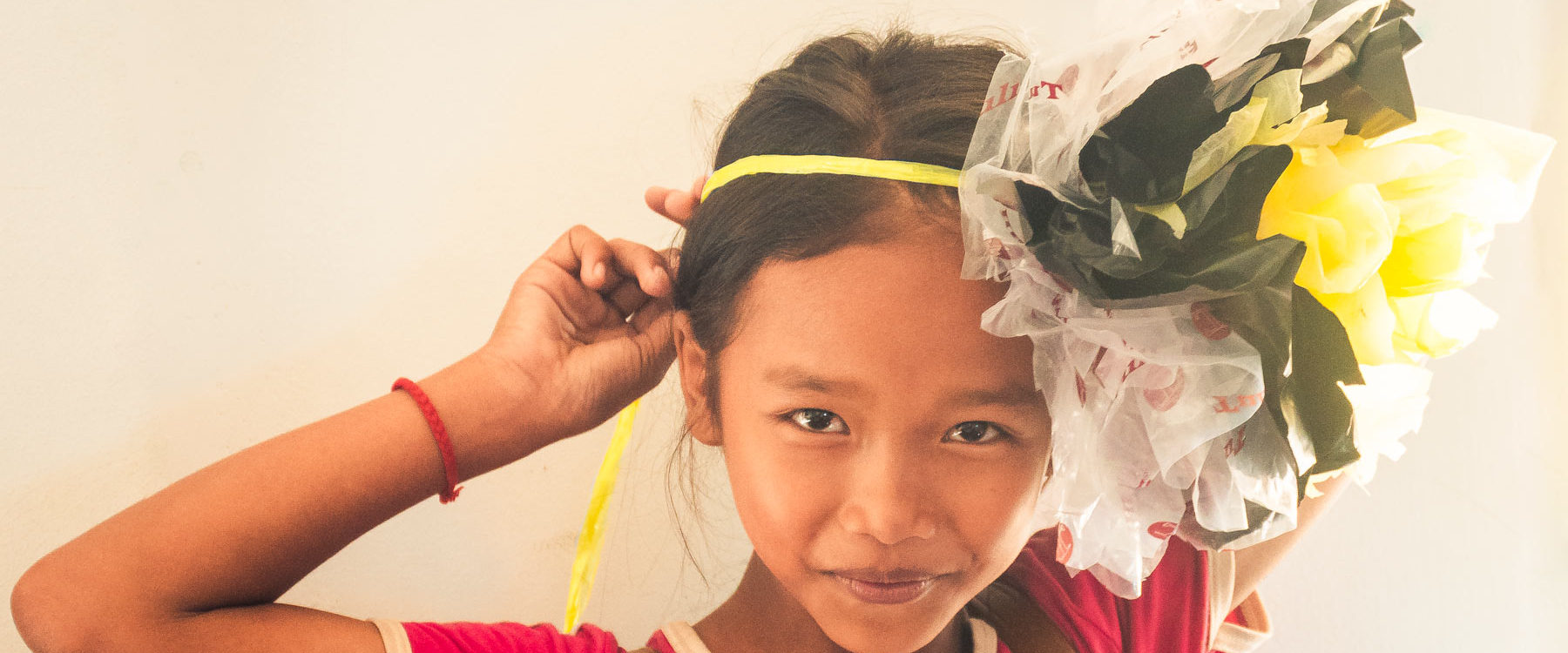 Happy kid is wearing a big flower made from plastic waste on her head and made during a craft course - fun filled ecological project in Phnom Penh, Cambodia