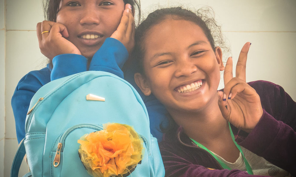 Khmer schoolgirls have hooked a crafted flower made from recycled plastic bags on a school bag during a ecological and creative children's course in Phnom Penh