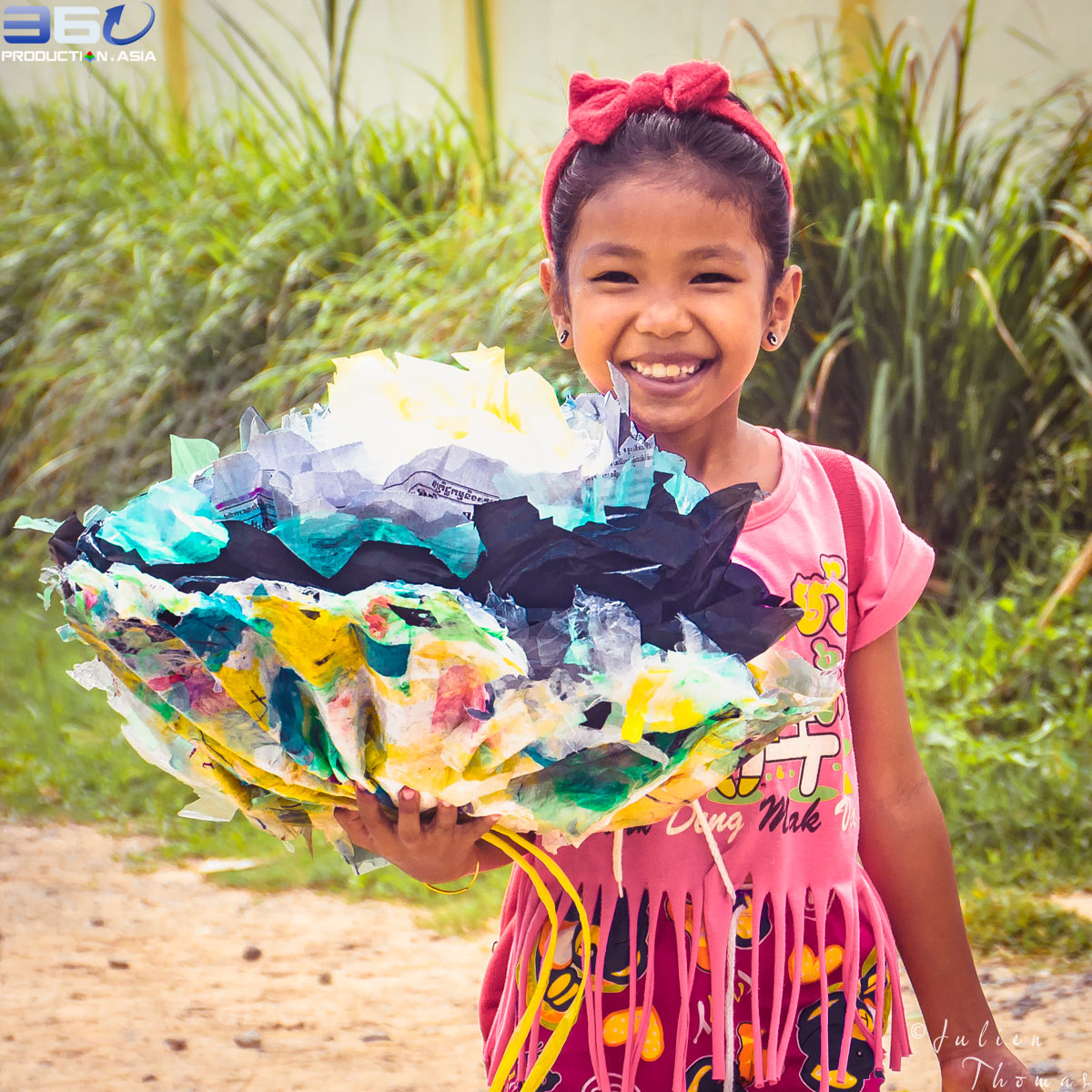 Cambodian participating girl is carrying a multicolor and large plastic flower made from upcycled waste material during a craft and creative course for children