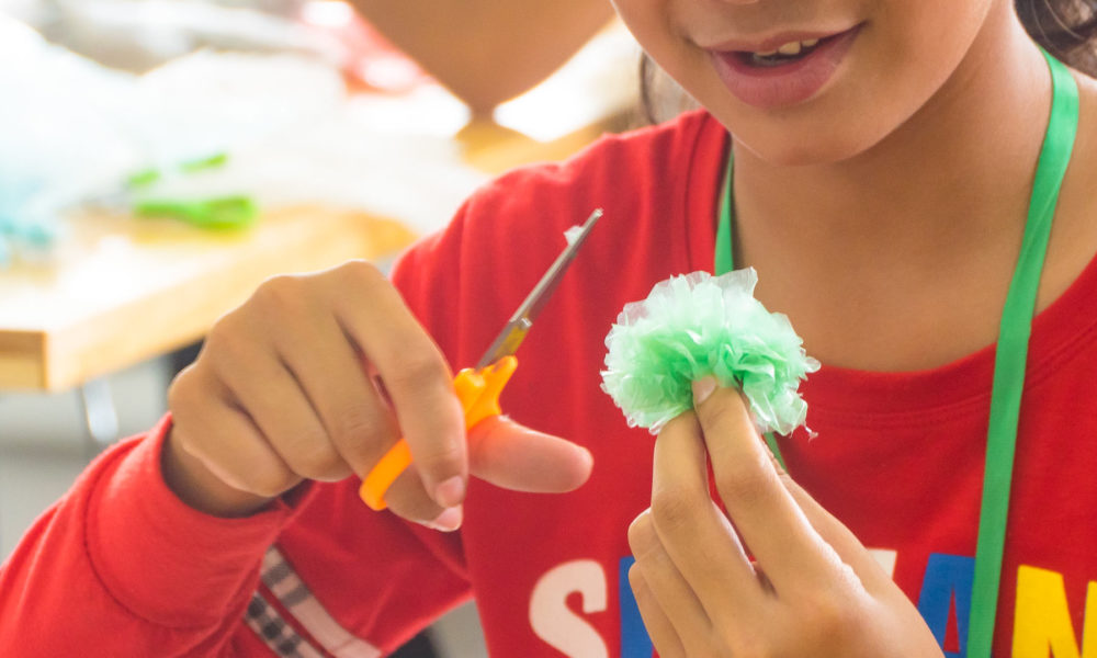 Student is finishing to create her plastic flower from recycled - upcycled plastic waste during a fun filled ecological and crafty project by Julien Thomas