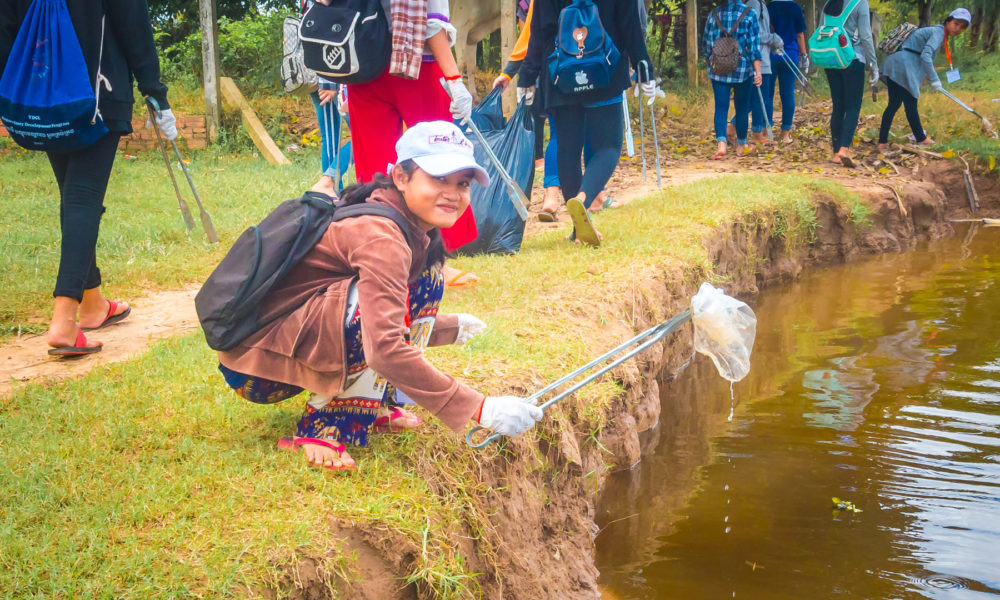 """Schoolgirl from NGO """"Toutes à L'école"""" is picking up a discarded plastic bag in a river in Cambodia during a fun filled and ecological course by Julien Thomas."""