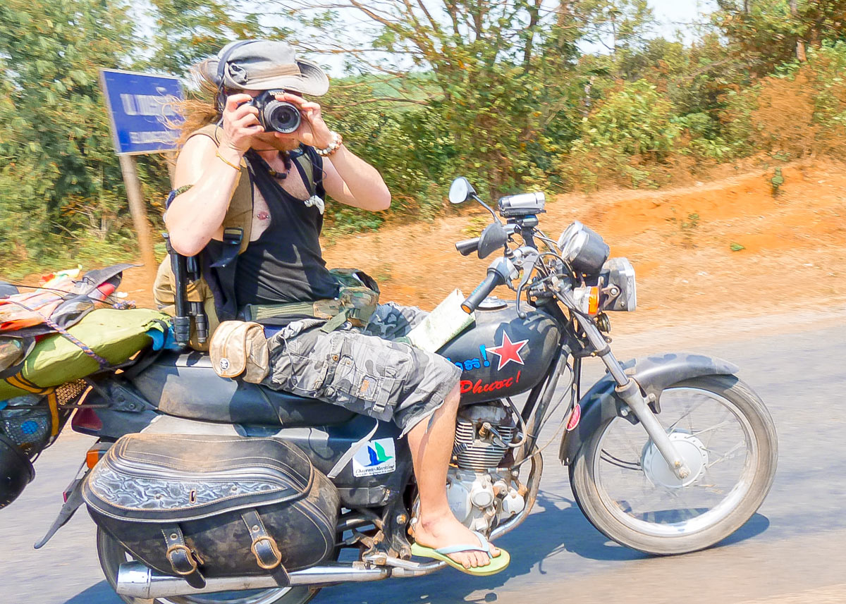 Julien Thomas drive motorbike Bonus with a red Vietnamese stars and a Charente Maritime sticker, he is taking a photo while driving in Laos.
