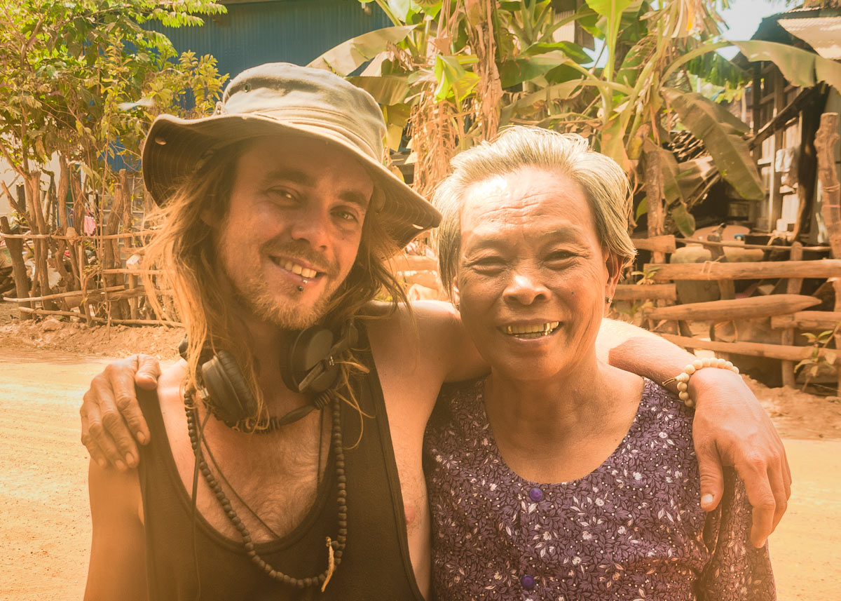 Julien Thomas with a local old Khmer women. They are happy and smiling in a remote local village near dirt track, travel road in Cambodia.