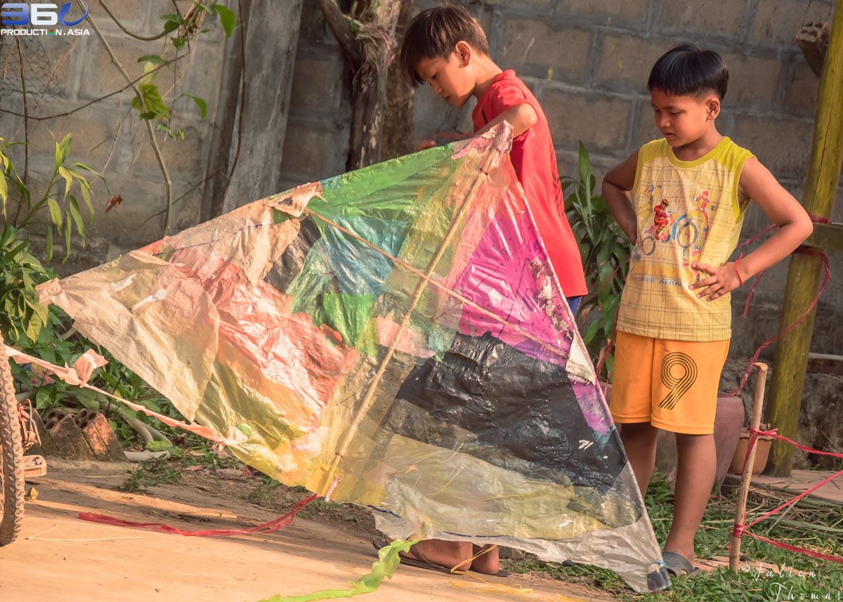 Two young boys and a large children's kite made from environmental plastic waste bags during a fun filled ecological project in Cambodia by Julien Thomas
