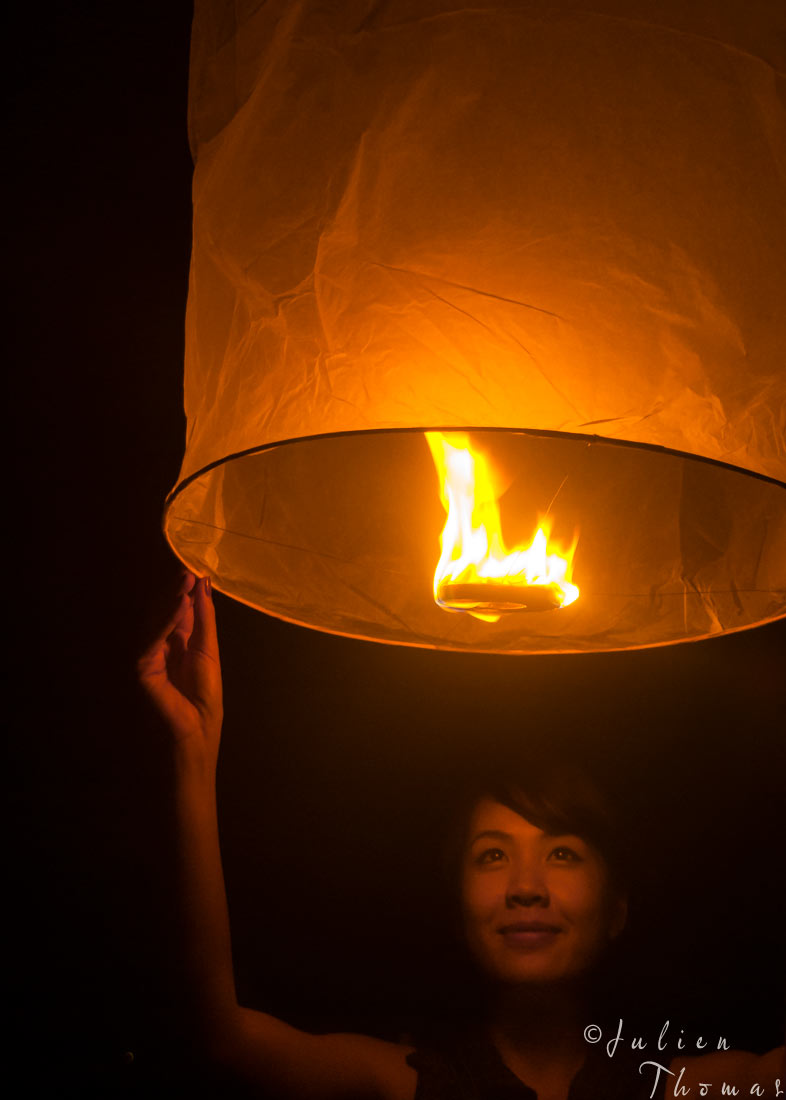 Teenager Laotian girl holding a traditional sky lantern, hot air balloon made of paper ready to fly during an annual cultural event - first Festival in Wat Phu.