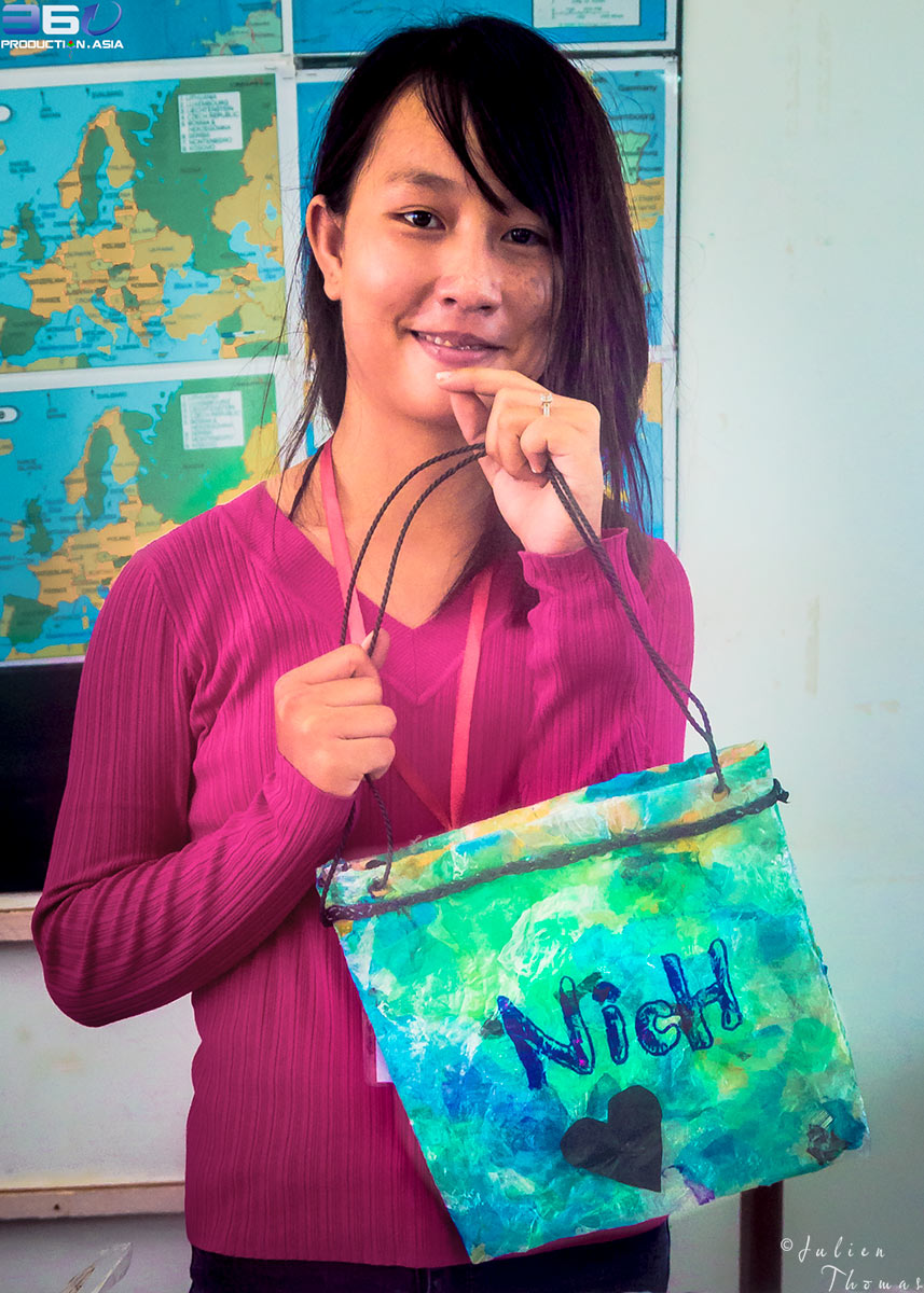 Cambodian girl with her homemade purse she did crafted using plastic waste materials during a creative and upcycle - recycle course in Phnom Penh.