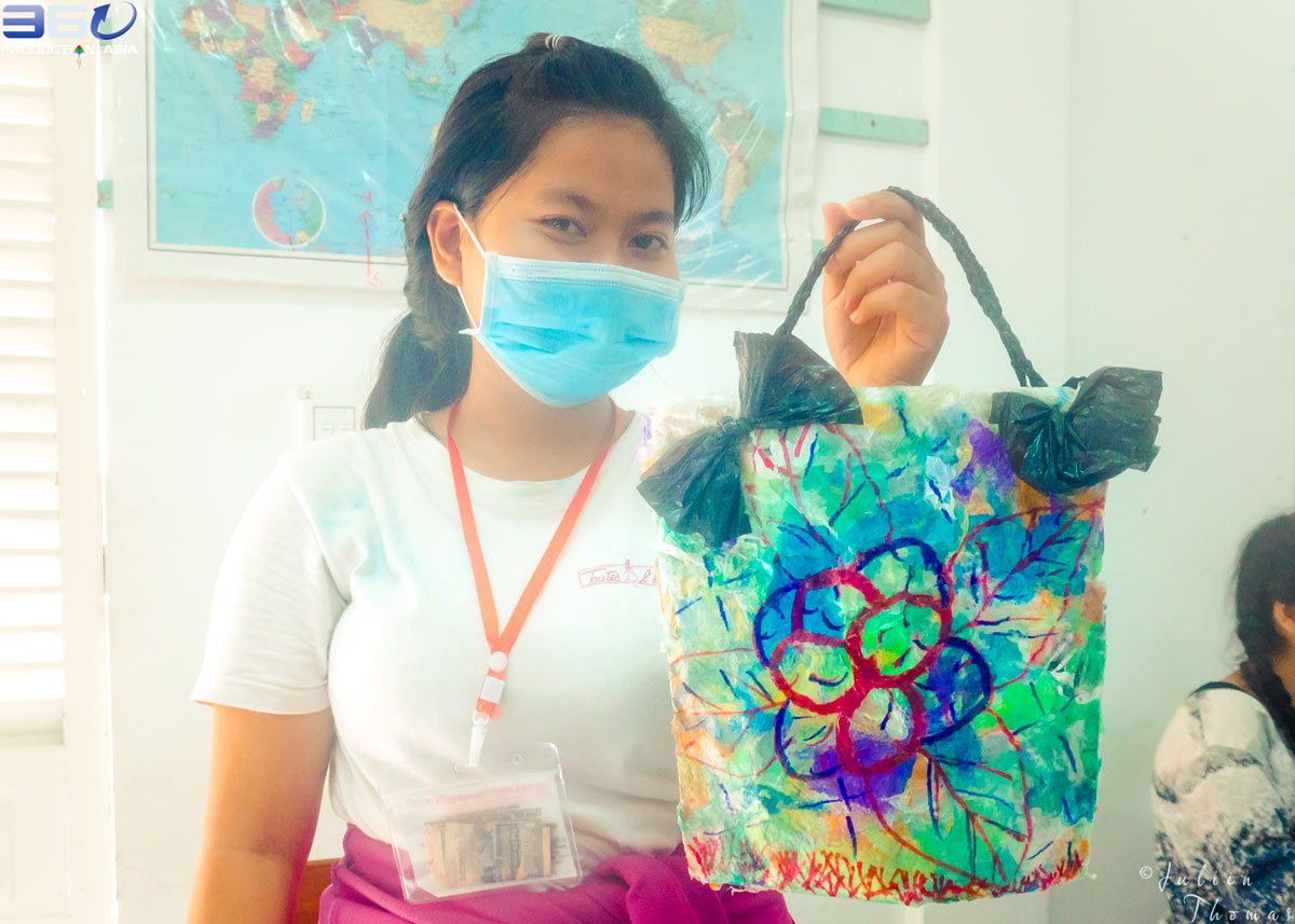 "Student from ""Toutes à L'école"" NGO with her crafted purse made from plastic waste material during a creative activity and ecological course for children."