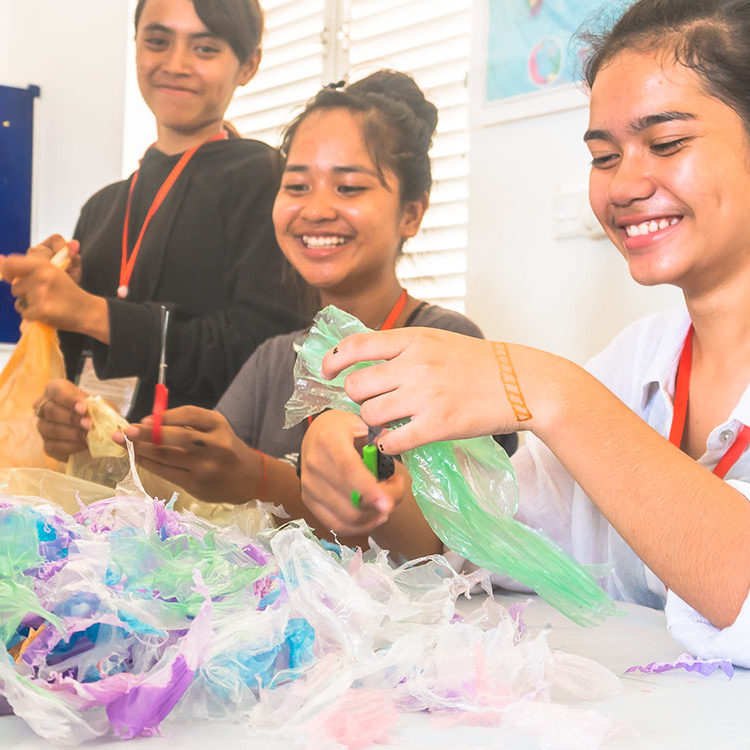 Cambodian schoolgirls are cutting and processing plastic waste during a craft and ecological course - project for children in their school at Phnom Penh.