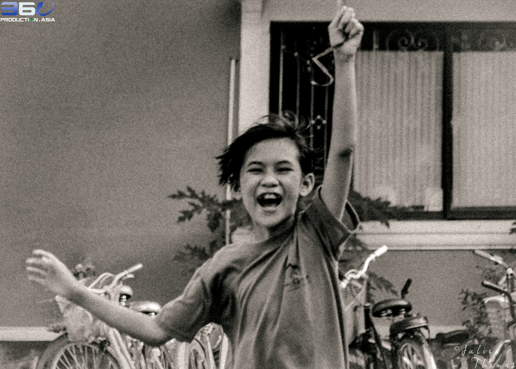 Child run with big smile very excited play with a kite in Maison Chance Vietnam by Julien Thomas