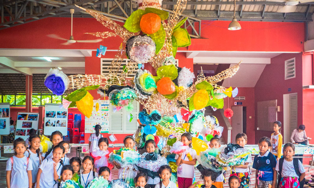 Participated schoolchildren whose have created large flowers from recycled plastic waste to hang on a crafted tree standing in Happy Chandara schoolyard