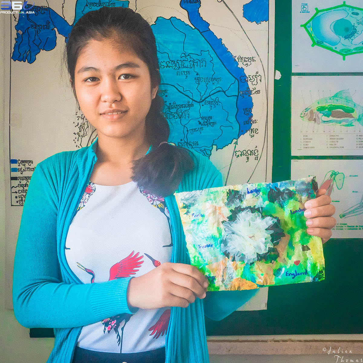 Schoolgirl with her homemade plastic purse made from upcycled waste material during a recycle and ecological course for children in Phnom Penh, Cambodia.