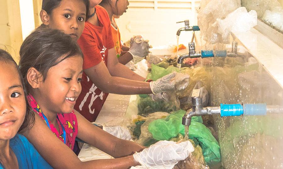 Group of students are cleaning the collected discarded plastic waste from their neighborhood community during an ecological project - course in Cambodia.
