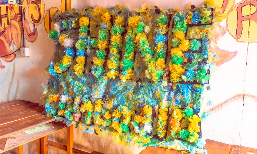 The children's creation with recycled plastic materials to create multicolor Flowers during a craft and ecological course in Shine Cambodia NGO, Otres Village.