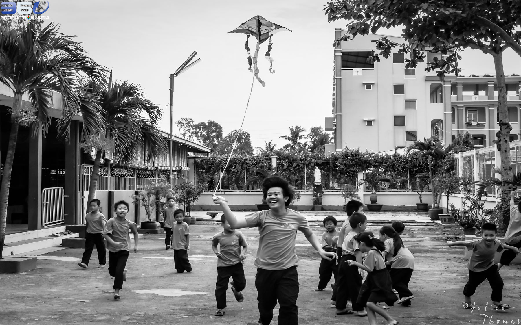 Joyful Vietnamese schoolchildren are playing with a homemade kite made with upcycled plastic bags during a fun filled ecological course in Ho Chi Minh City