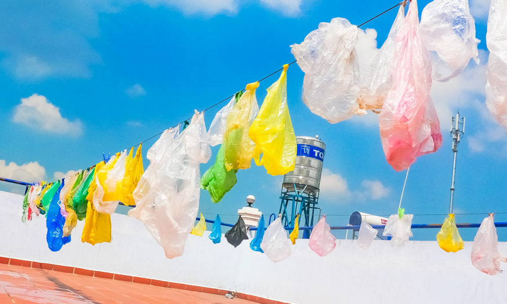 The cleaned plastic bags - plastic waste are hanging the schoolyard to get dried before to reuse them with schoolchildren into children's crafts in Southeast Asia.