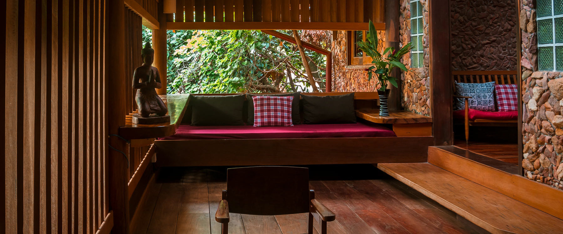 Private terrace to the garden in a wooden cottage with lounge area made of natural stones and wooden parquet in Veranda Natural Resort, Kep - Cambodia.