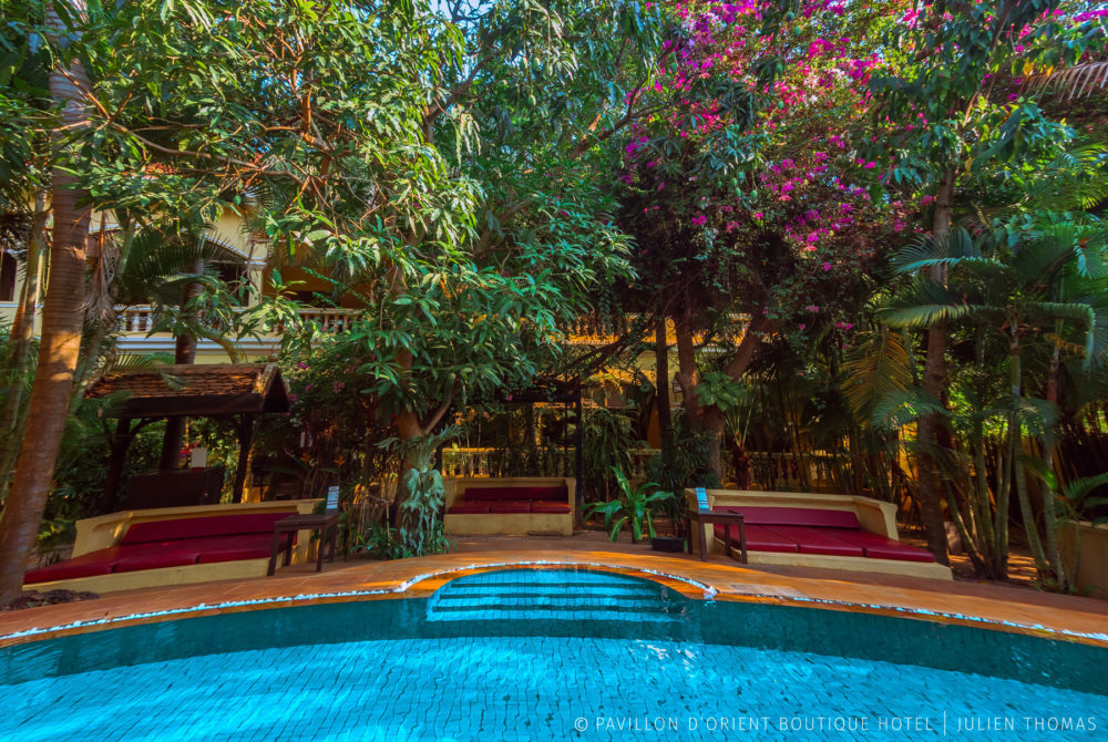 Swimming pool and garden area with surrounded by the accomodation for the tourists in holiday at Pavillon d'Orient Hotel Boutique, Siem Reap - Cambodia.