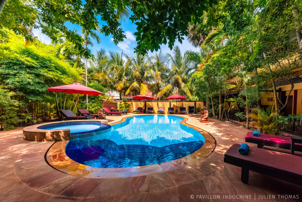 Swimming pool area with shade and trees in Pavillon Indochine, Siem Reap - Cambodia.